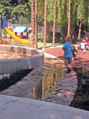 The faux creek takes water from the spray play area and allows children to follow it downstream.